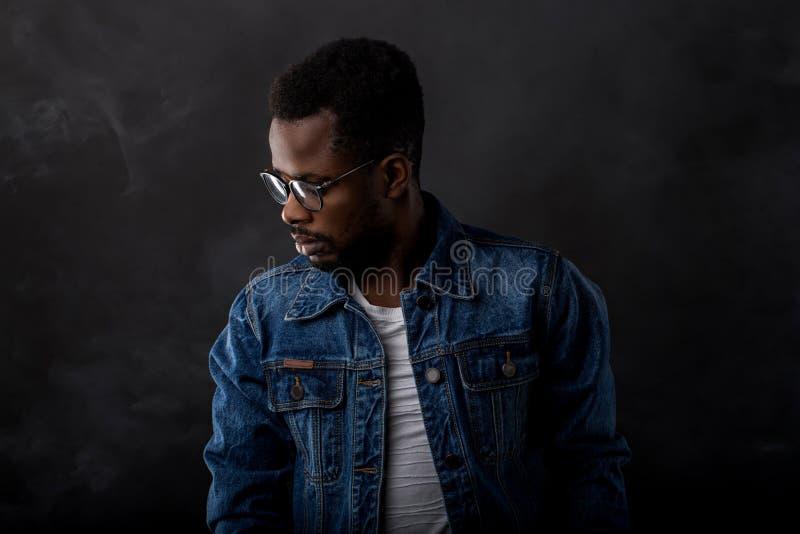 Portret van de knappe jonge Afrikaanse mens op zwarte achtergrond royalty-vrije stock afbeelding