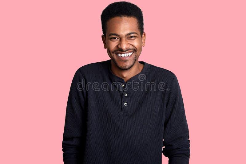 Portret van de knappe jonge donkere gevilde mens Het knappe lachende mannetje stelt in studio, hoort de kerel grappige grap Vroli royalty-vrije stock foto