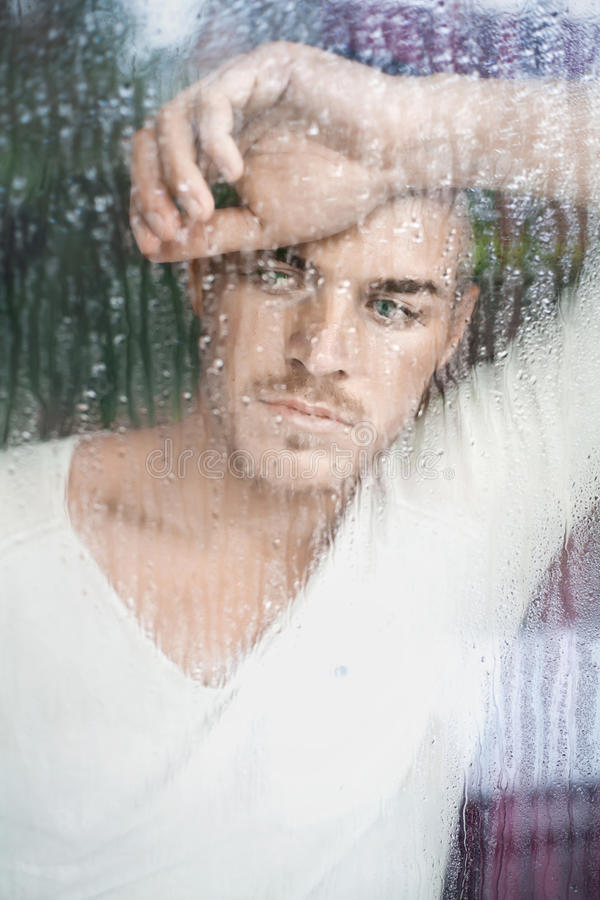 Portret van de knappe jonge mens die door natte windo kijken royalty-vrije stock foto