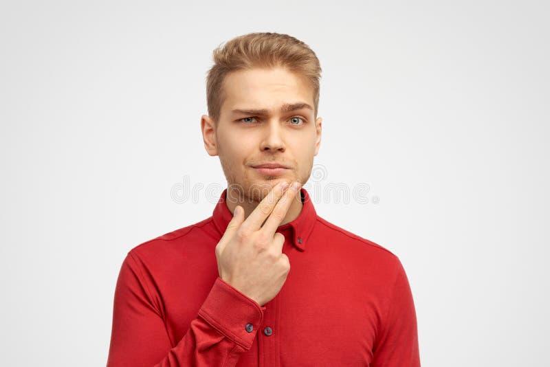 Portret van de knappe jonge mens die nadenkende uitdrukking, het fronsen heeft geconcentreerd, die haar vingers houdt op haar kin royalty-vrije stock fotografie