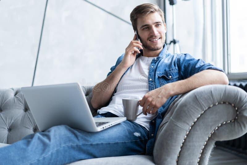 Portret van de knappe jonge mens die telefoneren en zijn laptop met behulp van terwijl thuis het zitten op bank royalty-vrije stock foto
