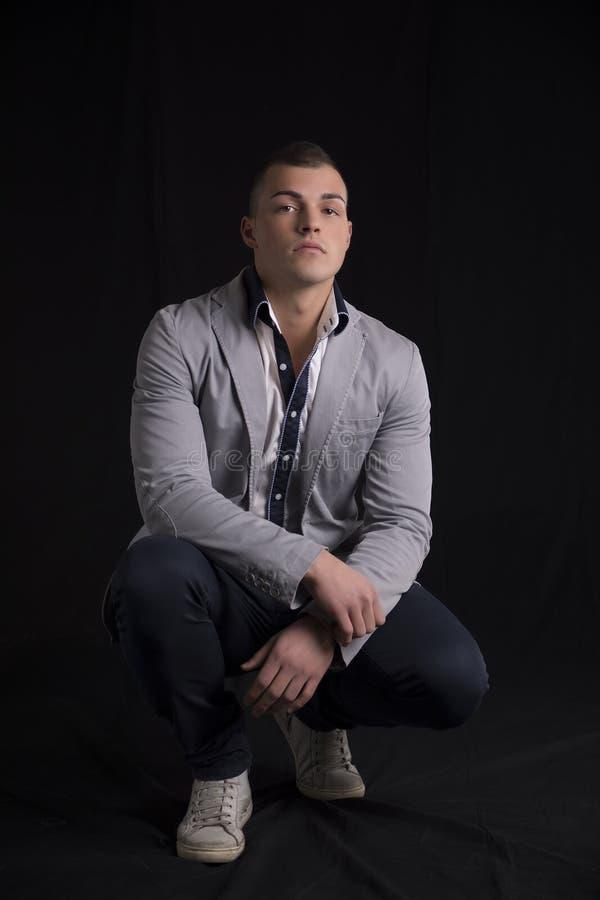 Portret van de knappe jonge mens met overhemd en jasjezitting op zijn hielen royalty-vrije stock foto's