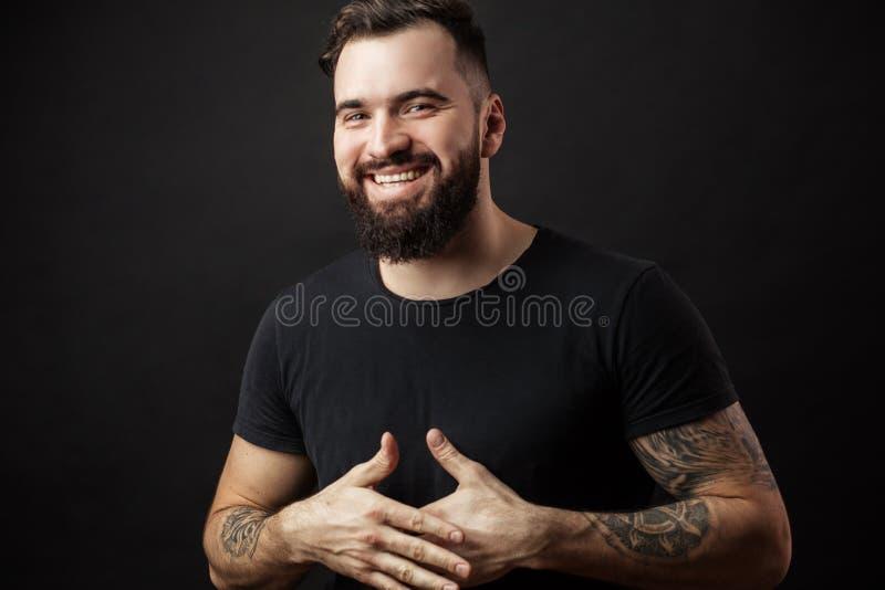 Portret van de knappe jonge mens in toevallige t-shirt over zwarte achtergrond stock foto's