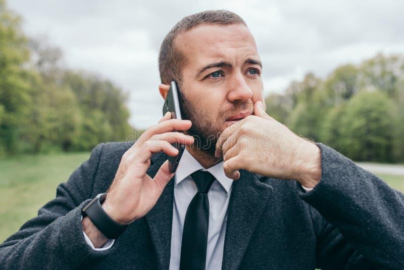 Portret van de knappe jonge stedelijke Europese professionele mens die mobiel gadget in openlucht gebruiken royalty-vrije stock foto's