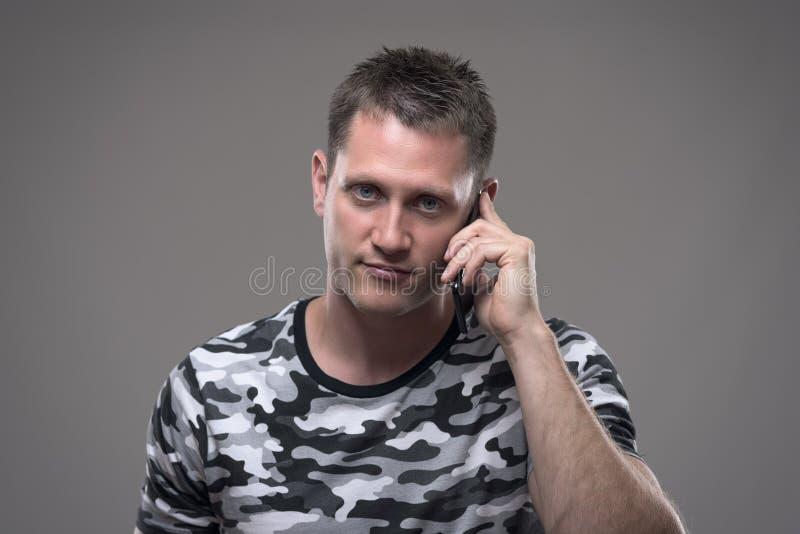 Portret van de knappe jonge volwassen mens die op het mobiele telefoon en het glimlachen bekijken camera spreken stock afbeelding