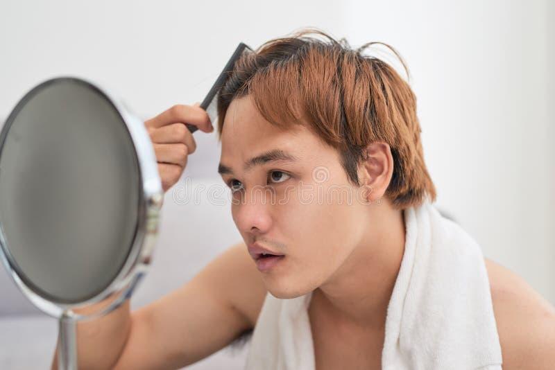 Portret van de knappe mens die zich in spiegel en brushi bekijken stock afbeeldingen