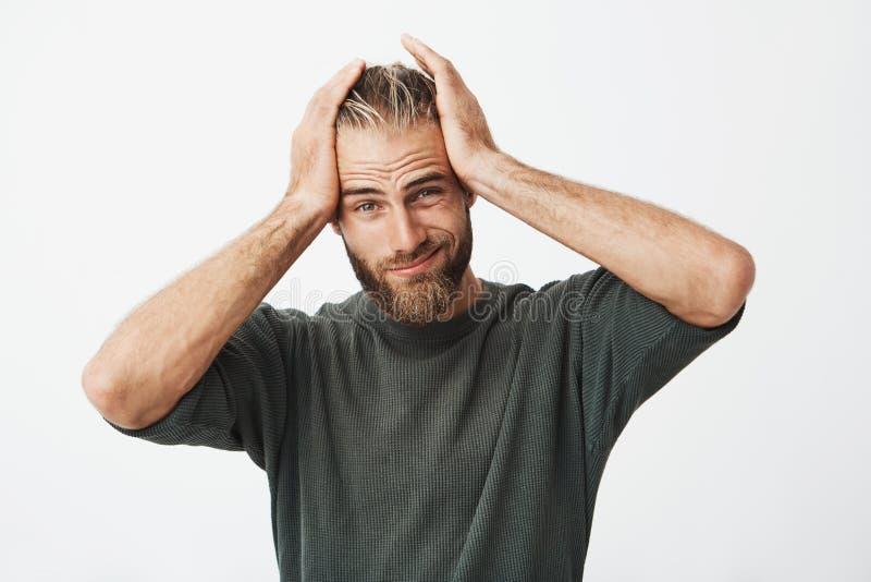 Portret van de knappe mens met modieus kapsel en baard die uitdrukking wegens hoofdpijn na harde dag hebben vermoeid stock afbeeldingen