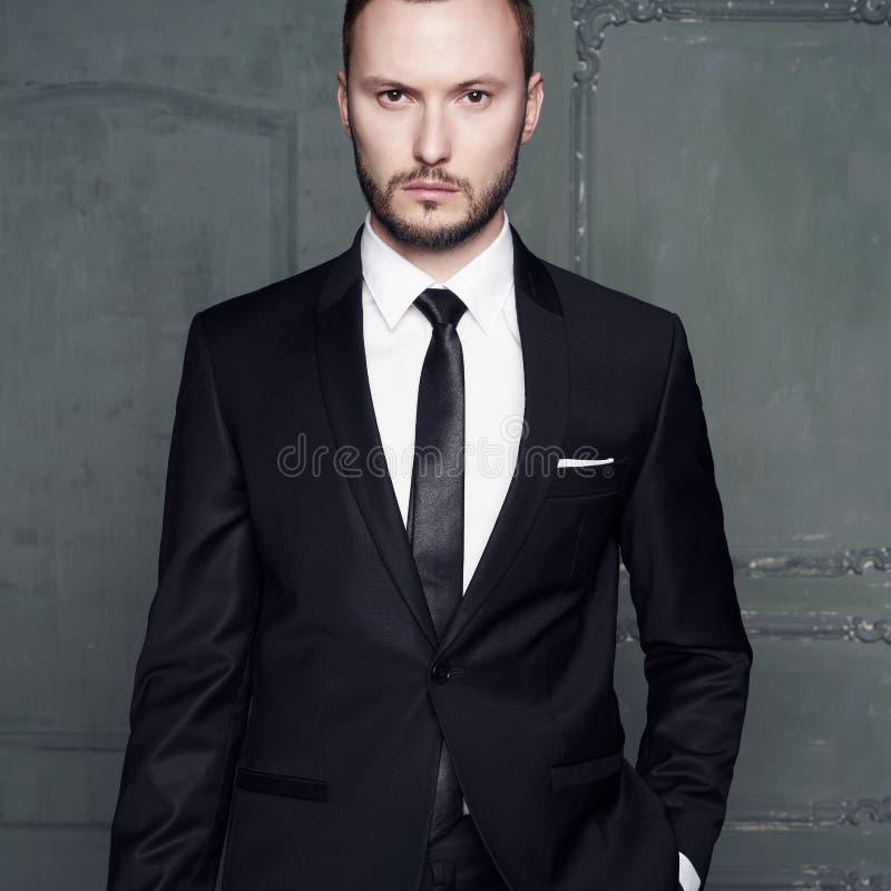 Portret van de knappe modieuze mens in elegant zwart kostuum stock foto