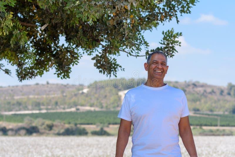 Portret van de Knappe Oude Actieve Hogere Mens in openlucht Hogere landbouwer die zich op weideachtergrond bevindt stock fotografie