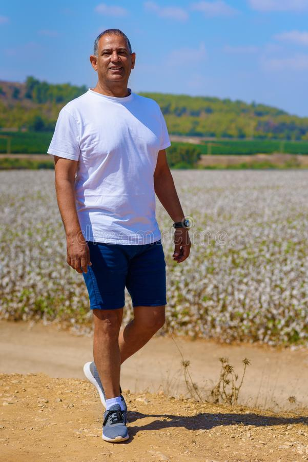 Portret van de Knappe Oude Actieve Hogere Mens in openlucht Sportieve atletische bejaarde zakenman die zich op weideachtergrond b stock afbeelding