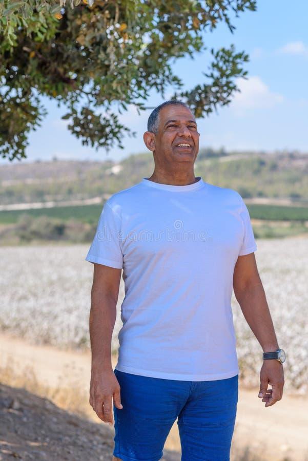Portret van de Knappe Oude Actieve Hogere Mens in openlucht Sportieve atletische bejaarde zakenman op aardachtergrond stock afbeelding