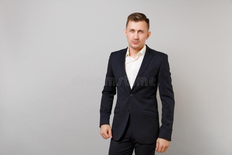 Portret van de knappe zekere jonge bedrijfsmens in klassieke zwarte kostuum witte overhemd status geïsoleerd op grijze muur royalty-vrije stock foto's