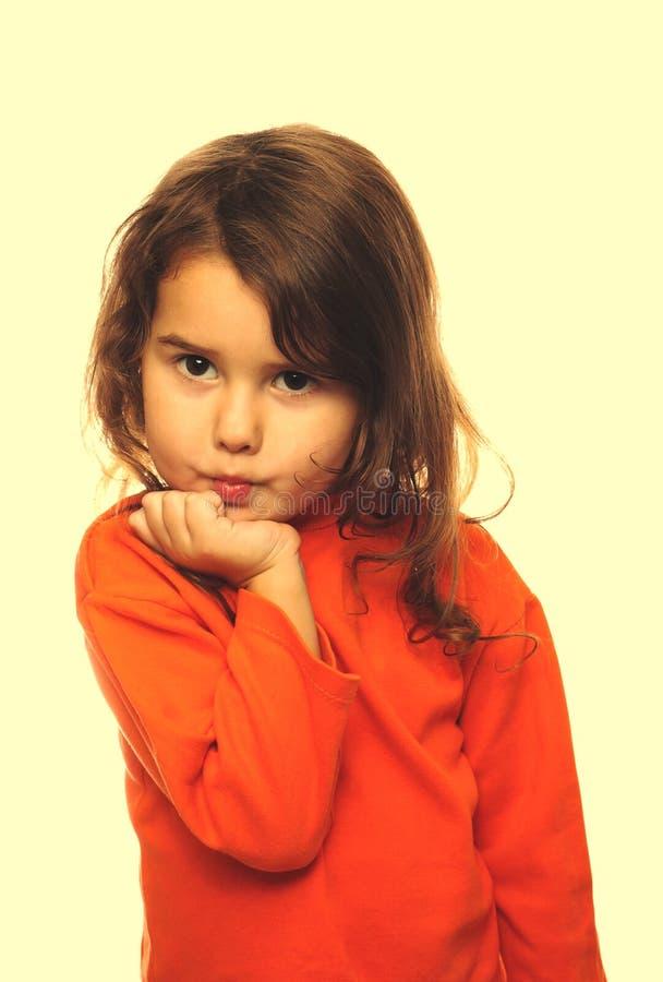 Portret van de krullende flirt van de de sweaterflirt van het donkerbruine meisjeskind oranje royalty-vrije stock fotografie