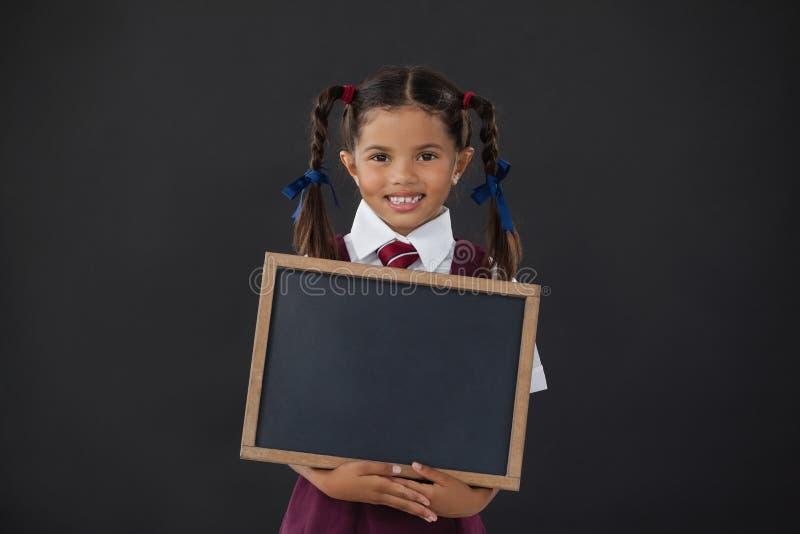Portret van de lege lei van de schoolmeisjeholding tegen bord stock afbeeldingen