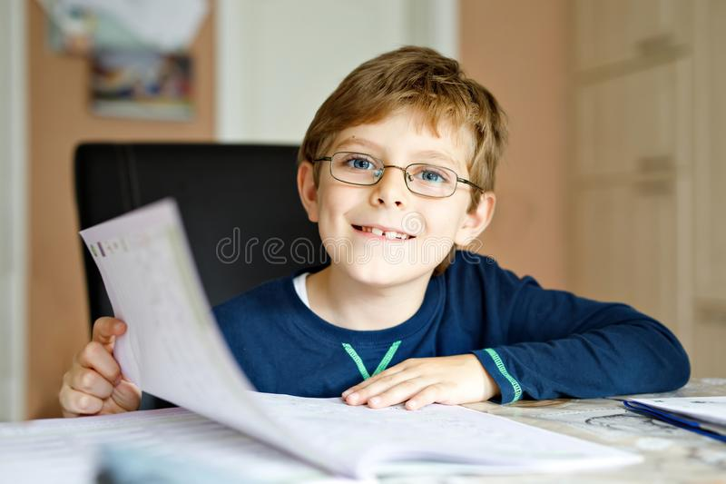 Portret van de leuke jongen die van het schooljonge geitje glazen dragen die thuis thuiswerk maken Weinig geconcentreerd kind die royalty-vrije stock afbeeldingen