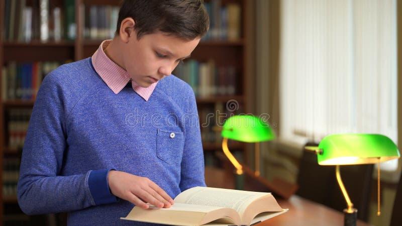 Portret van de leuke schooljongen en status dichtbij het boekenrek in de bibliotheek wordt geschoten en het lezen van een boek da stock foto