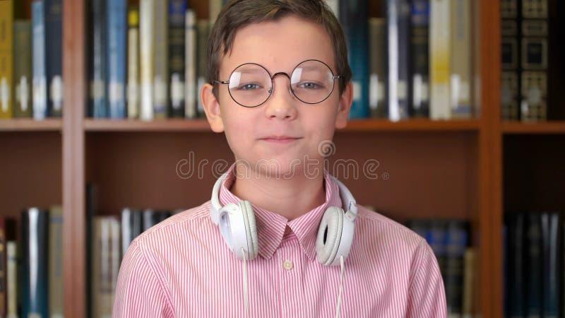 Portret van de leuke schooljongen wordt geschoten die zich dichtbij het boekenrek in de bibliotheek bevinden die royalty-vrije stock foto