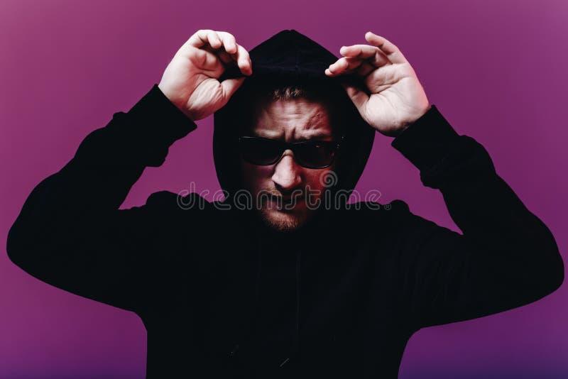 Portret van de maniermens in een zwarte sweater met een kap en zonnebril in neonlicht in de studio royalty-vrije stock foto