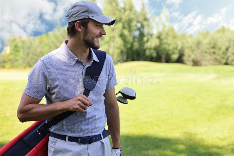 Portret van de mannelijke zak van het golfspeler dragende golf terwijl het lopen door groen gras van golfclub royalty-vrije stock foto's