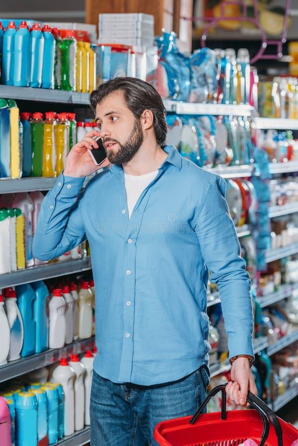 portret van de mens die op smartphone spreken terwijl het kiezen van detergentia royalty-vrije stock fotografie