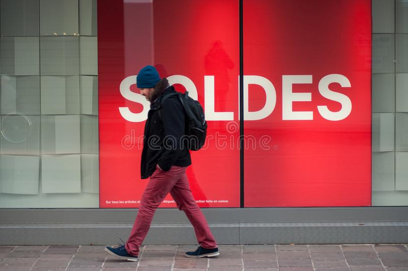 Portret van de mens die in de straat voor manieropslag lopen met tekst in de Franse kwaadsprekerij van 'SOLDES 'in Engelse Verkoo stock foto