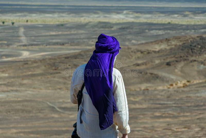 Portret van de mens in het witte shirt en blauwe tulband op zijn rug in de woestijn van Marokko royalty-vrije stock fotografie