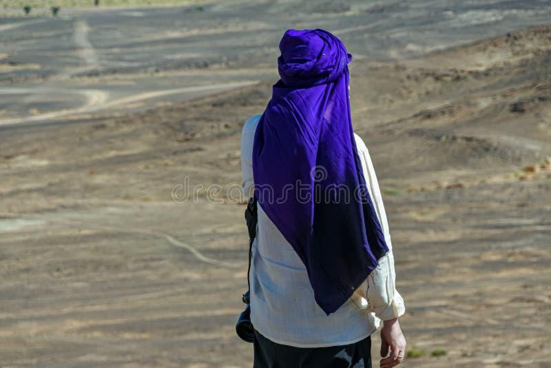 Portret van de mens in het witte shirt en blauwe tulband op zijn rug in de woestijn van Marokko royalty-vrije stock afbeelding
