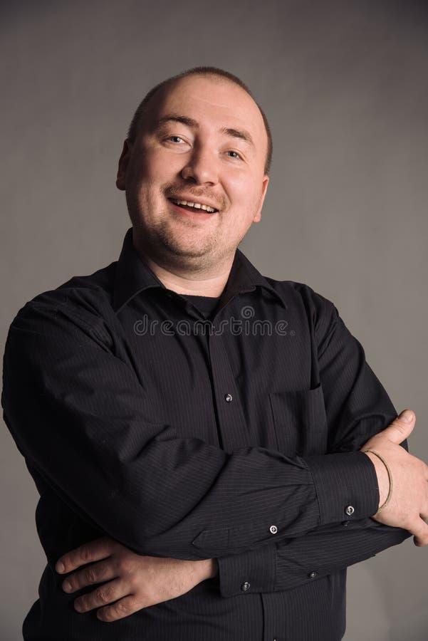 Portret van de mens in zwart overhemd bij het grijze studio stellen als achtergrond aan de camera stock afbeeldingen