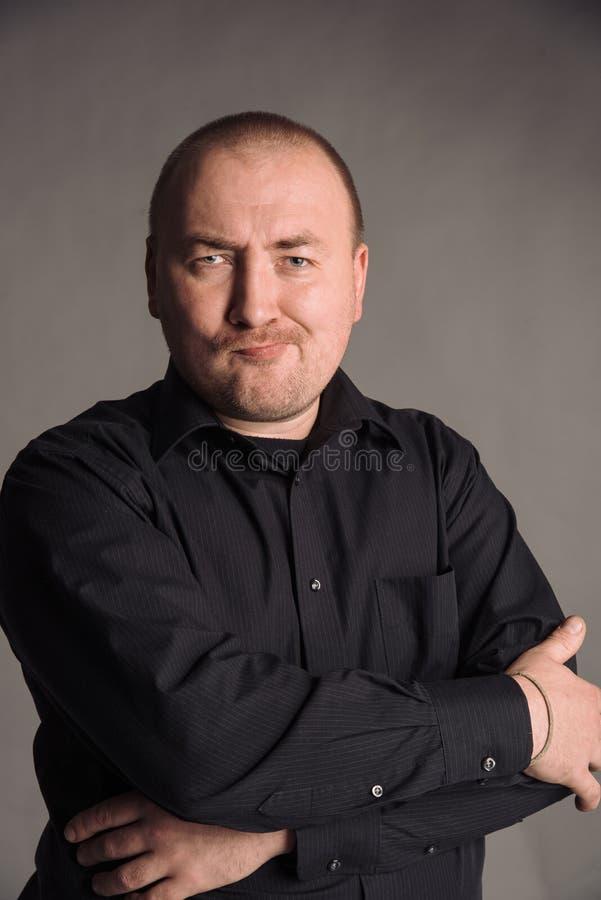 Portret van de mens in zwart overhemd bij het grijze studio stellen als achtergrond aan de camera royalty-vrije stock fotografie