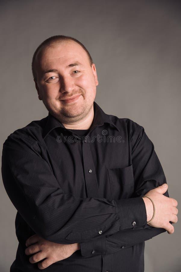 Portret van de mens in zwart overhemd bij het grijze studio stellen als achtergrond aan de camera royalty-vrije stock afbeeldingen