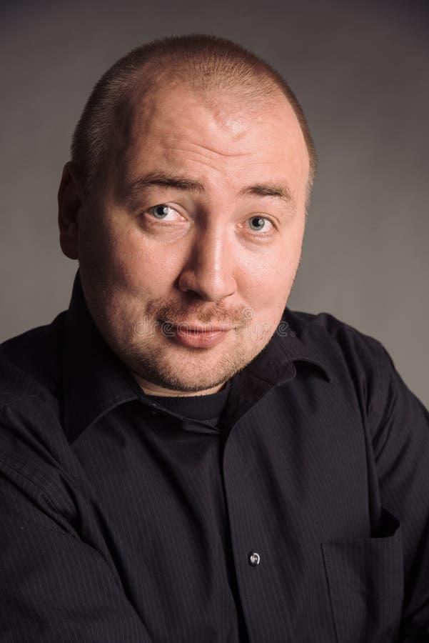 Portret van de mens in zwart overhemd bij het grijze studio stellen als achtergrond aan de camera royalty-vrije stock afbeelding