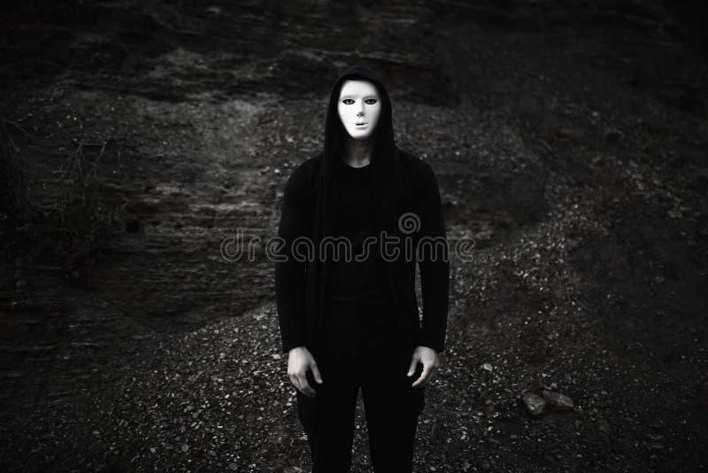 Portret van de mens in zwarte hoodie die wit anoniem masker dragen stock fotografie