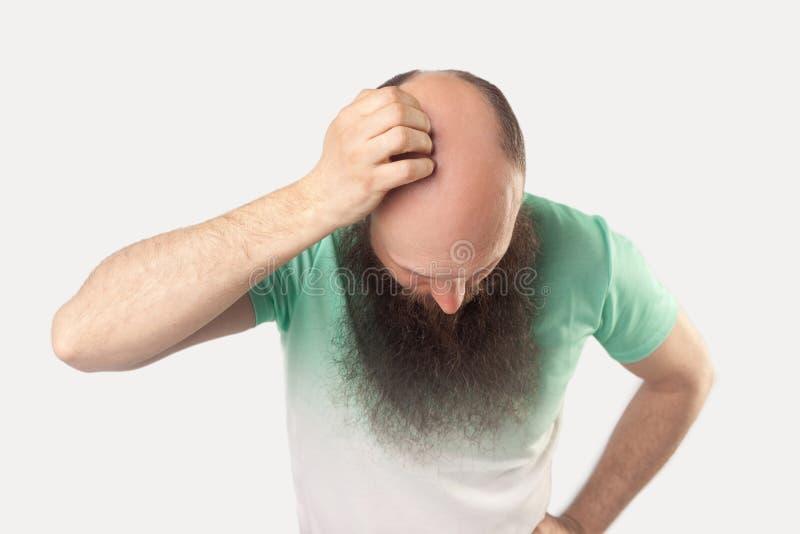 Portret van de midden oude kale mens met lange baard in lichtgroene t-shirt die en zijn kaalheid op zijn hoofd bevinden zich tone stock afbeeldingen