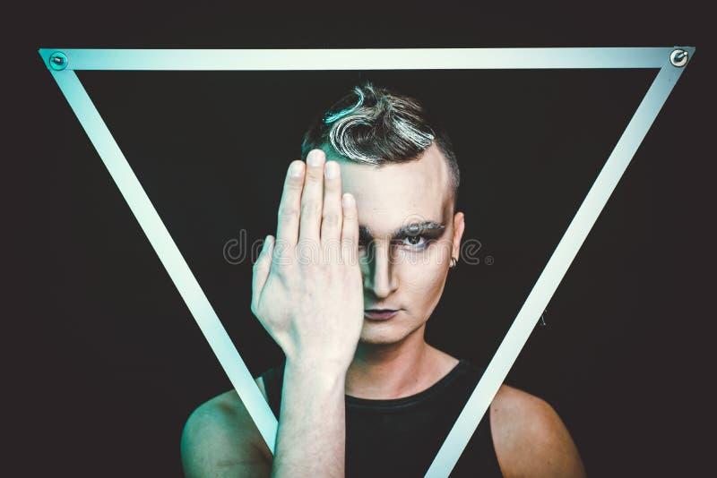 Portret van de mooie jonge mens met modern kapsel, artistieke veelkleurige make-up Het schot van de studio royalty-vrije stock afbeelding