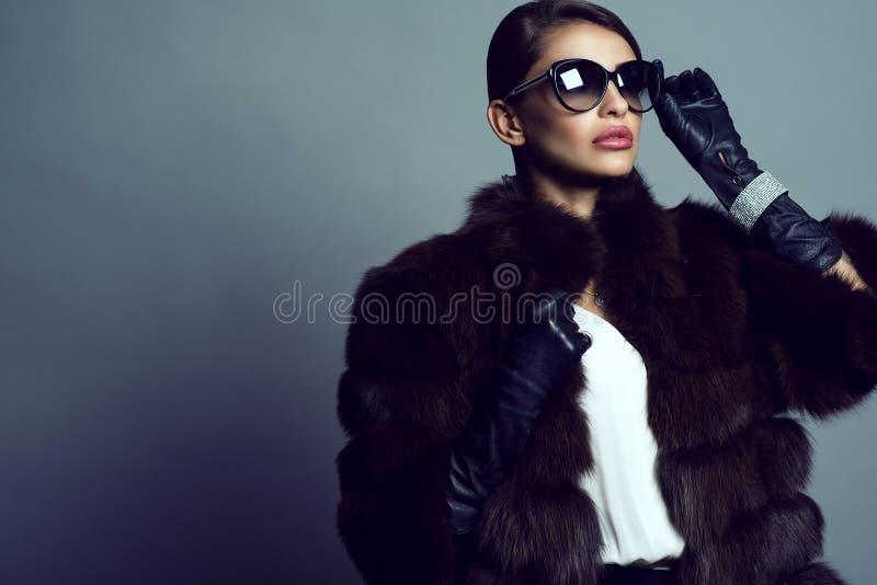 Portret van de mooie laag, de zonnebril, de handschoenen en de juwelen van de glam model dragende sabelmarter stock fotografie