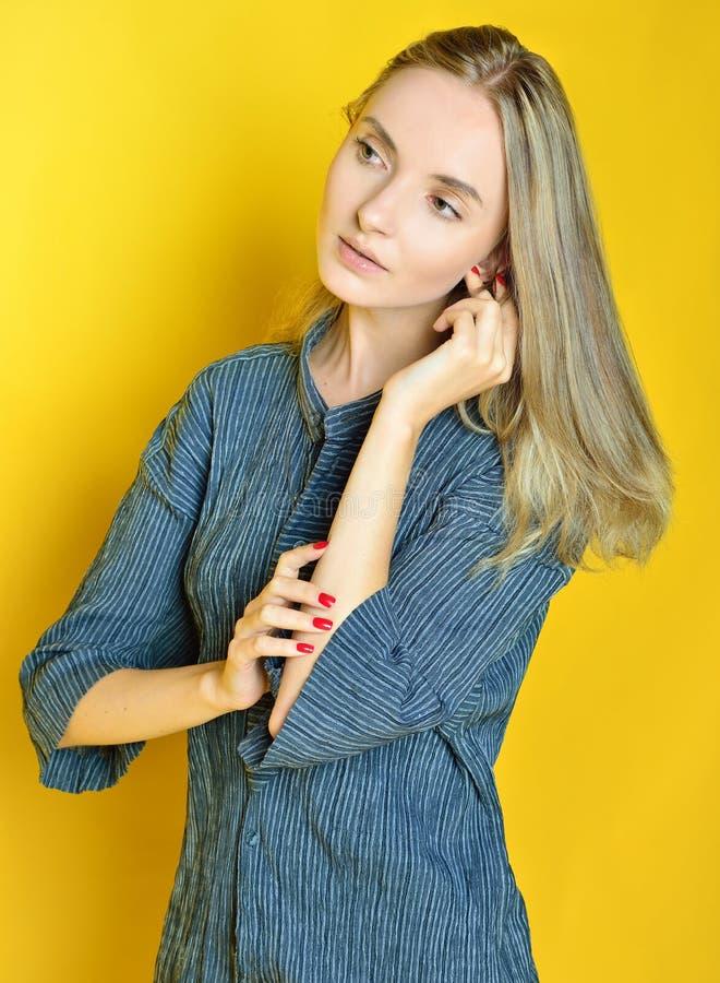 Portret van de mooie vrouw met gele achtergrond stock foto