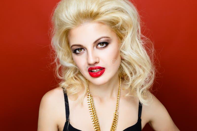 Portret van de mooie vrouw van de blonde glam tuimelschakelaar op oranje achtergrond stock fotografie