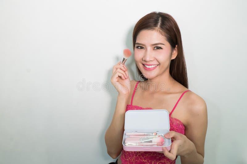 Portret van de mooie vrouwelijke model Geplaatste borstels van de holdingssamenstelling royalty-vrije stock foto's