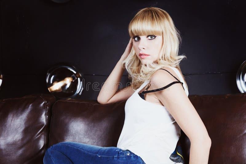 Portret van de mooie zitting van het blondemeisje op bank stock afbeelding