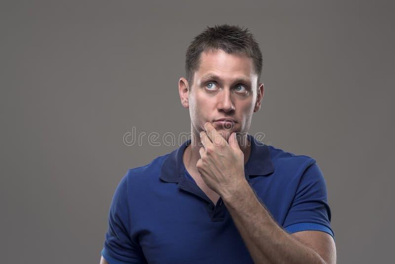 Portret van de nadenkende ernstige onzekere jonge volwassen mens die omhoog denkend met hand op kin kijkt stock fotografie