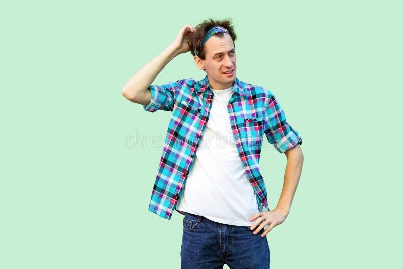 Portret van de nadenkende jonge mens in toevallig blauw geruit overhemd en hoofdband die, zijn hoofd krassen en wat denken om te  royalty-vrije stock afbeeldingen