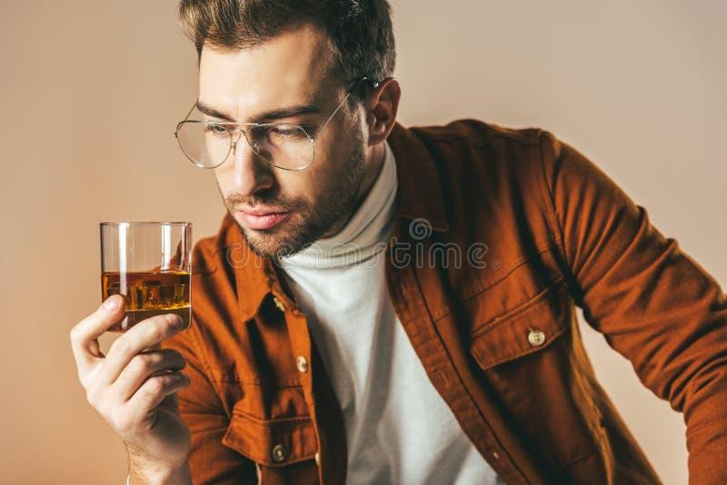 portret van de nadenkende modieuze mens die glas cognac ter beschikking bekijken royalty-vrije stock foto's