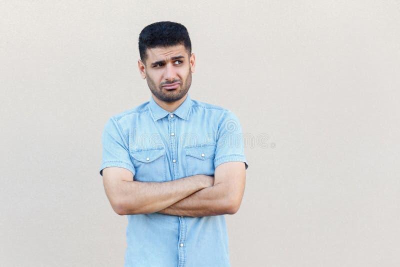 Portret van de nadenkende verwarde knappe jonge gebaarde mens in blauw overhemds zich bevindt, gekruiste wapens, weg kijkend en d stock afbeeldingen