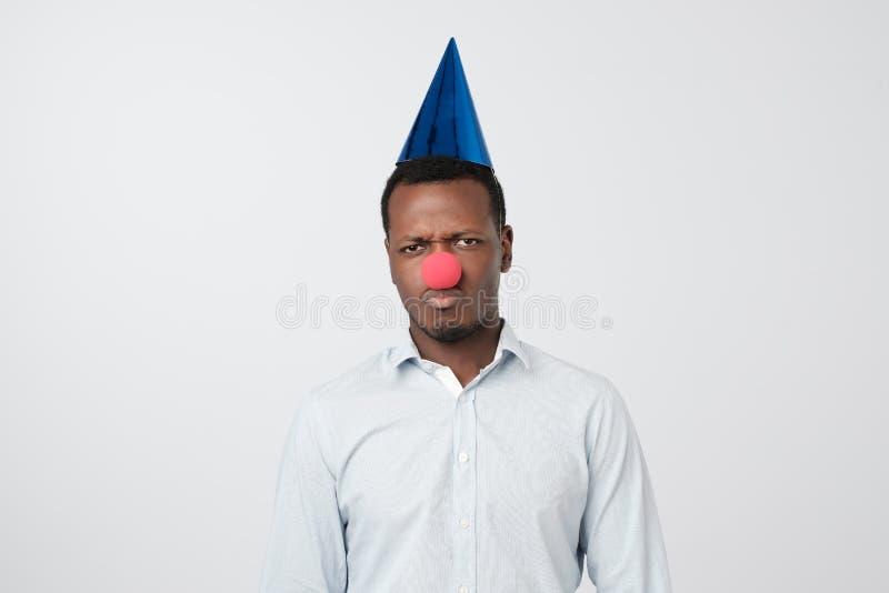 Portret van de ongelukkige Afrikaanse mens met een rode neus die al dwazendag vieren stock foto