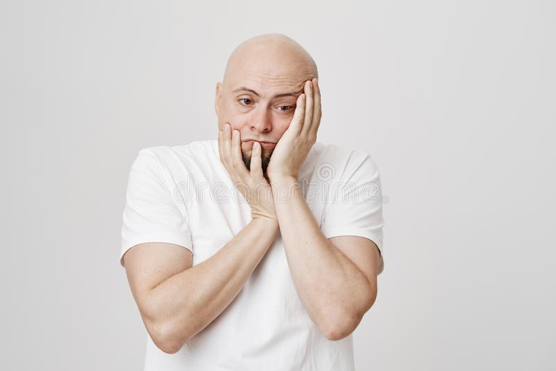 Portret van de ongelukkige vermoeide kale mens die bored en verwoest terwijl het drukken en wat betreft gezicht en neer het kijke stock afbeeldingen