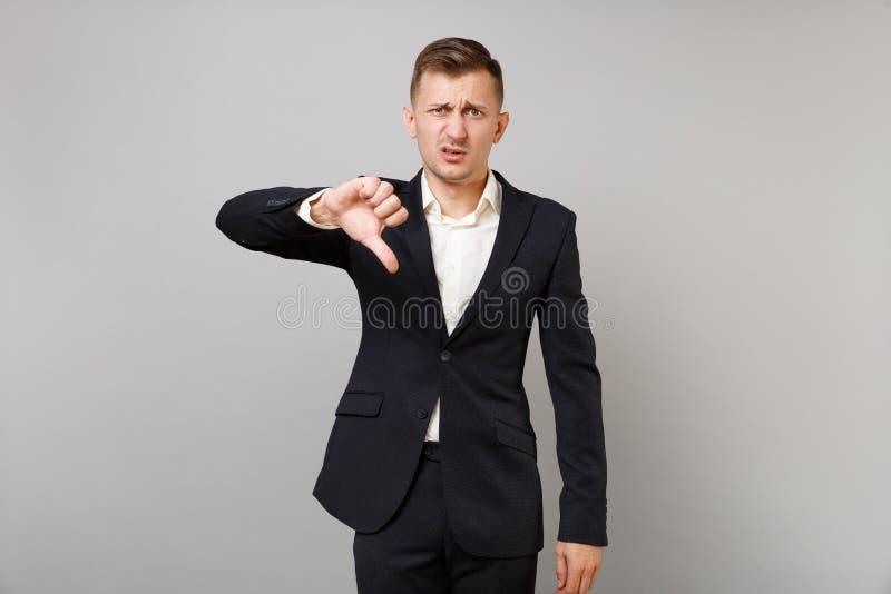 Portret van de ontevreden jonge bedrijfsmens in klassiek zwart kostuum, overhemd die die duim tonen neer op grijze muur wordt geï stock foto's