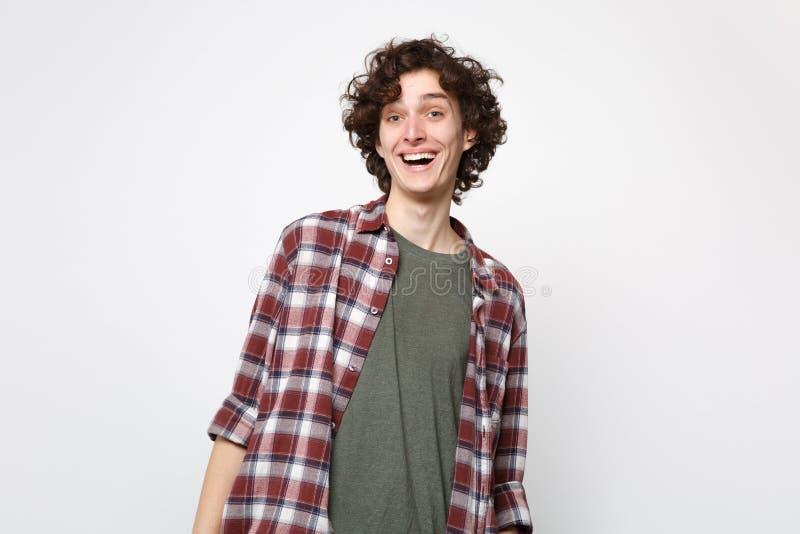 Portret van de opgewekte grappige lachende jonge mens in en vrijetijdskleding die camera bevinden die kijken op witte muur wordt  stock afbeeldingen