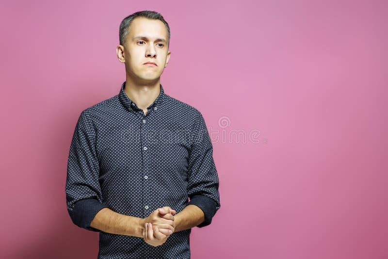 Portret van de peinzende jonge mens op roze achtergrond royalty-vrije stock foto's