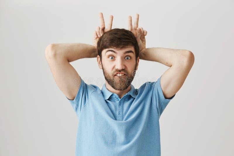 Portret van de positieve grappige gebaarde handen van de kerelholding achter hoofd en tonende voortanden alsof hij konijn, het ma royalty-vrije stock afbeeldingen