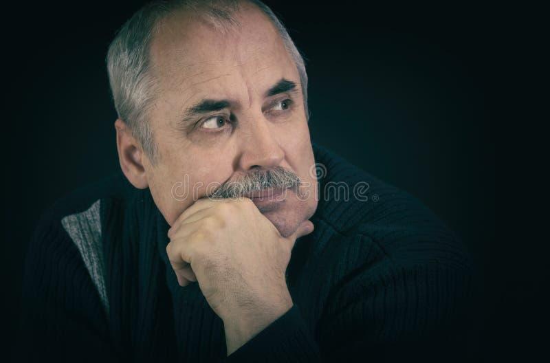 Portret van de rijpe Kaukasische mens die in darknes denken stock afbeelding